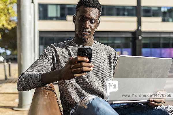 Young man sitting on a bench in the city  using laptop and smartphone