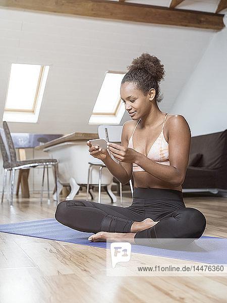 Junge Frau sitzt auf Yogamatte und benutzt Mobiltelefon
