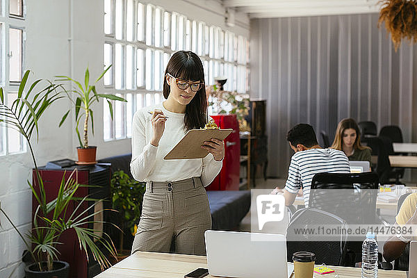 Woman with clipboard among colleagues in office