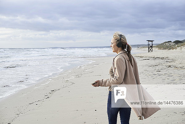 Spain  Menorca  senior woman using smartphone and wireless headphones on the beach in winter