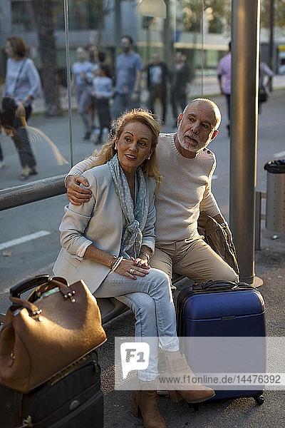 Spanien  Barcelona  älteres Ehepaar mit Gepäck wartet an der Straßenbahnhaltestelle in der Stadt