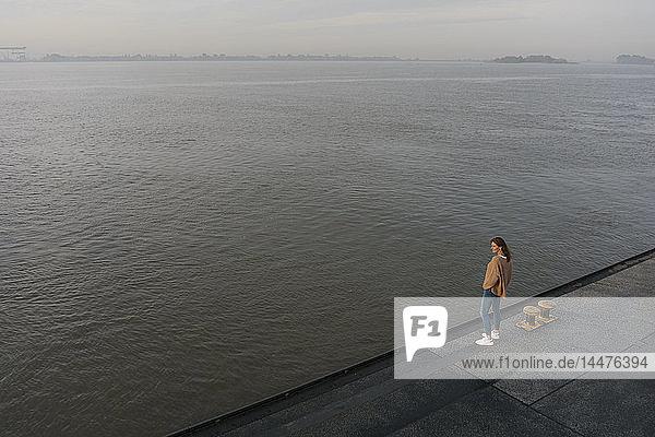 Deutschland  Hamburg  Draufsicht auf eine Frau am Elbufer am Pier stehend