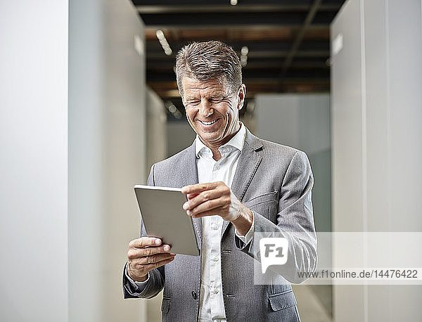 Smiling businessman using tablet on office floor