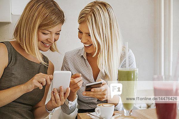 Zwei glückliche junge Frauen mit Smartphones in einem Cafe