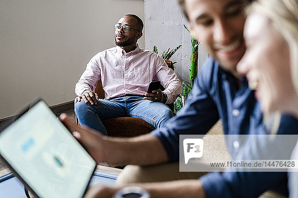 Businessman holding cell phone in loft office with colleagues in foreground