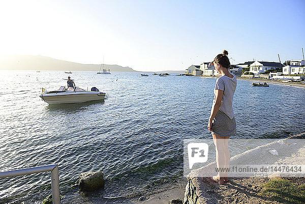 Junge Frau steht an der Küste und sieht einen Mann auf einem Boot im Meer an