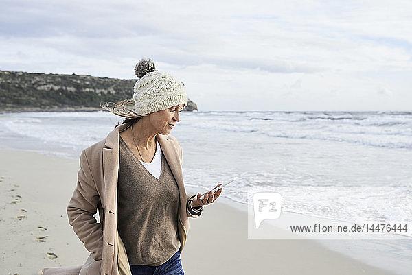 Spanien  Menorca  ältere Frau liest im Winter E-Book am Strand