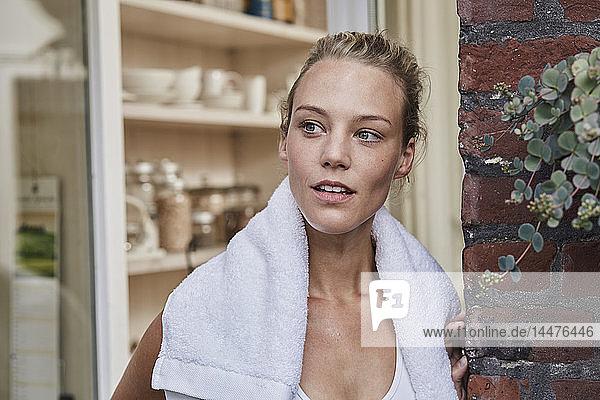 Porträt einer sportlichen jungen Frau mit Handtuch um den Hals am Hauseingang