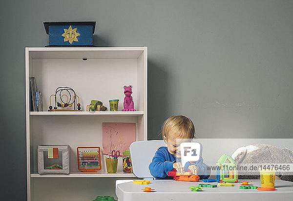 Lächelndes Mädchen spielt mit Knetmasse im Kinderzimmer