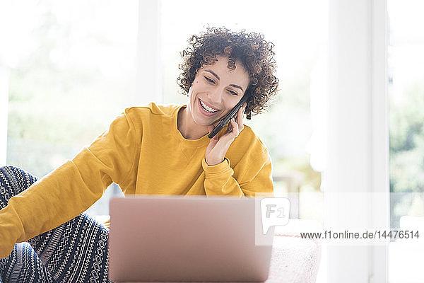 Glückliche Frau benutzt Laptop und Handy zu Hause
