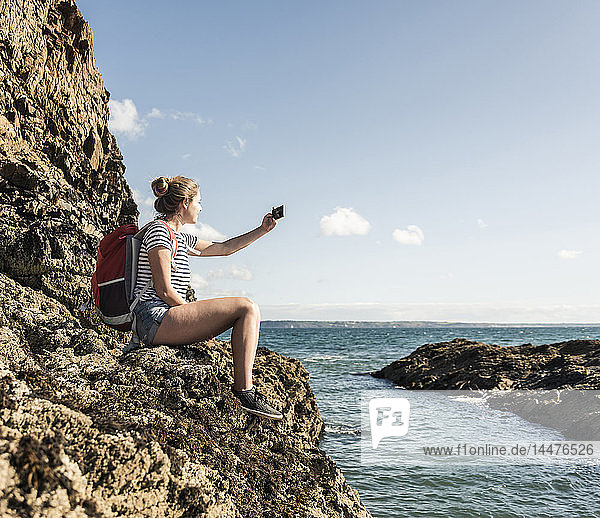 Young woman sitting on a rocky beach  taking pictures with her smartphone