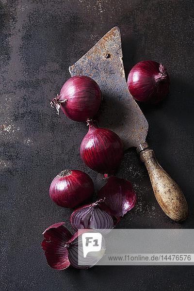 Ganze und in Scheiben geschnittene rote Zwiebeln und ein rostiges Hackebeil