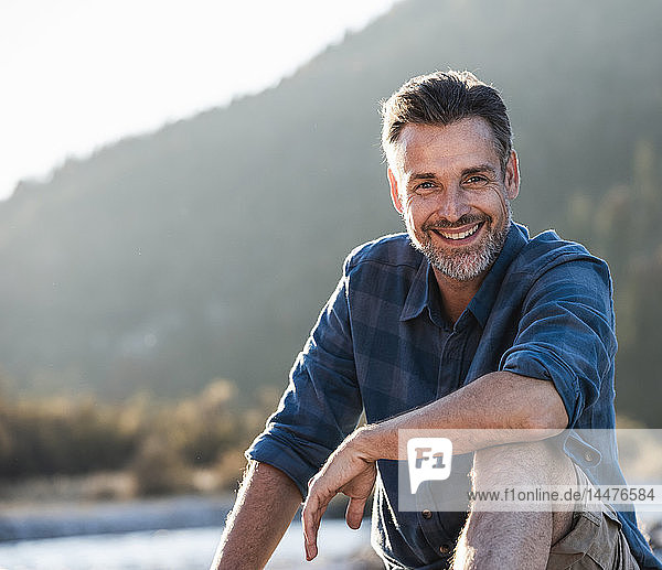 Erwachsener Mann zeltet am Flussufer