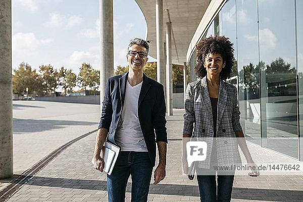 Porträt von zwei glücklichen Kollegen vor dem Bürogebäude