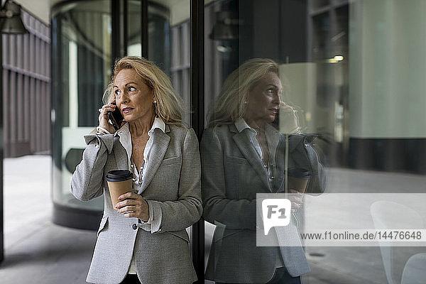An die Glasfront gelehnte ältere Geschäftsfrau telefoniert mit dem Handy