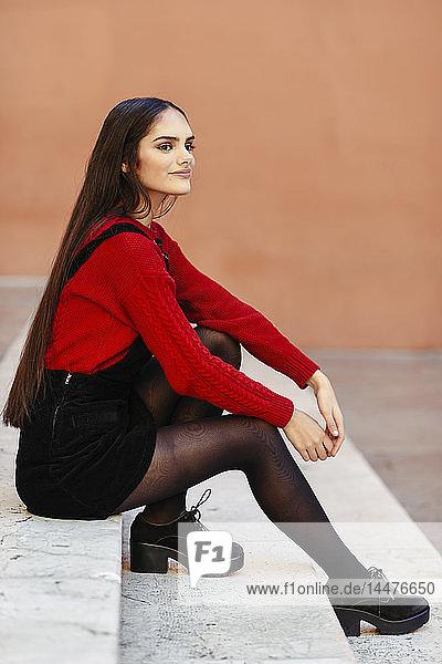 Porträt einer eleganten jungen Frau  die auf einer Treppe sitzt