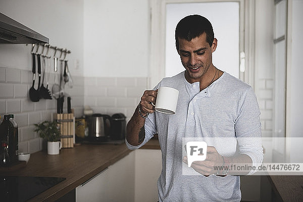 Smiling young man with cup of coffee using cell phone in kitchen at home