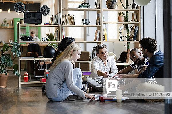 Geschäftsteam sitzt auf dem Boden und bespricht Dokumente im Loft-Büro