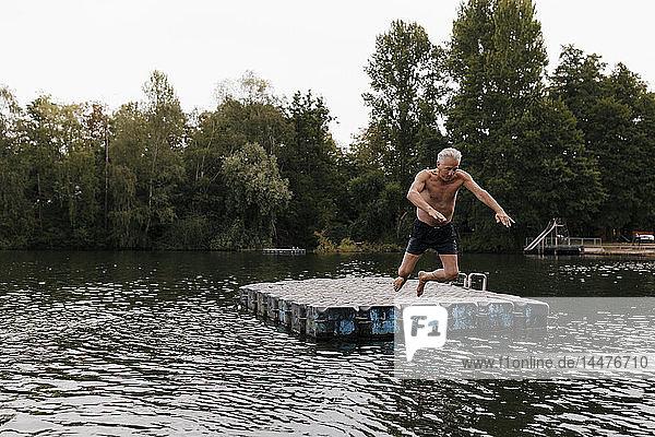 Älterer Mann springt in einem See vom Floß