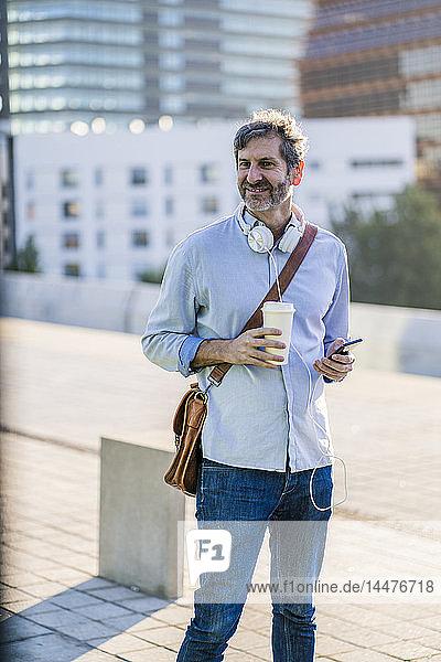 Porträt eines lächelnden reifen Mannes mit Kaffee zum Mitnehmen  Kopfhörer und Mobiltelefon in der Stadt