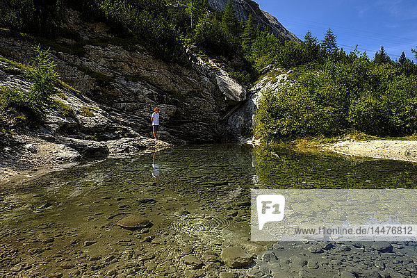 Italy  South Tyrol  Dolomites  young hiker standing on a source