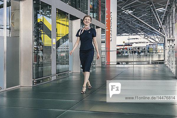 Porträt eines lächelnden Mitarbeiters einer Fluggesellschaft  der auf dem Flughafen spazieren geht