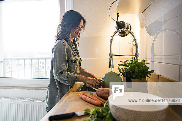 Woman rinsing pot in the sink of her kitchen