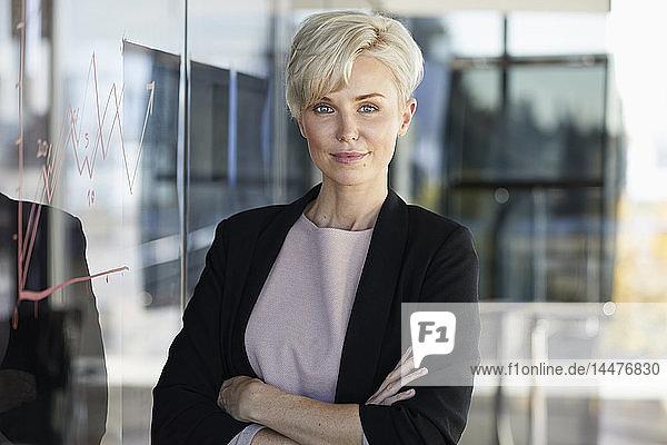 Porträt einer selbstbewussten Geschäftsfrau neben der Grafik auf einer Glasscheibe im Büro