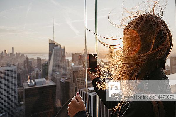 USA  New York  New York City  Frau  die bei Sonnenaufgang ein Foto macht
