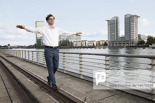 Deutschland  Berlin  Geschäftsmann balanciert auf einer Schiene an der Spree