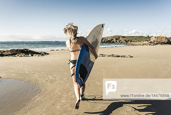 Young woman running on the beach  carrying surfboard