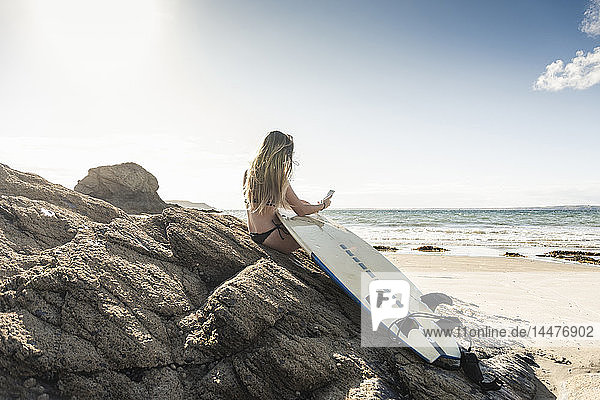Young woman with surfboard sitting on a rock at the beach  using smartphone