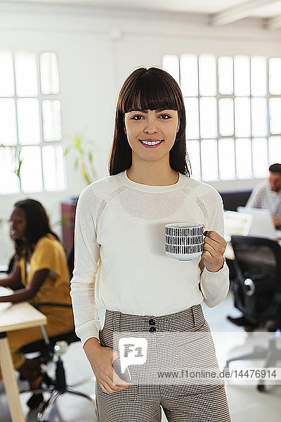 Portrait of smiling young woman in office with colleagues in background