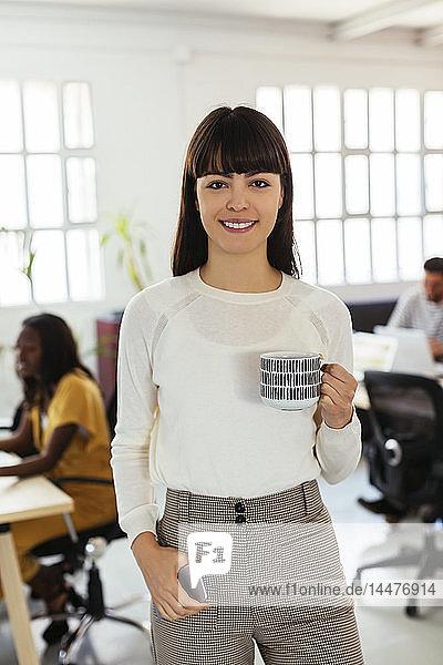 Porträt einer lächelnden jungen Frau im Amt mit Kollegen im Hintergrund