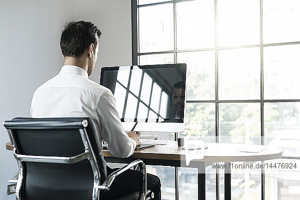 Businessman in office working on computer in front of window
