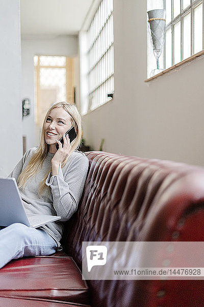 Smiling young woman sitting on couch with laptop talking on cell phone