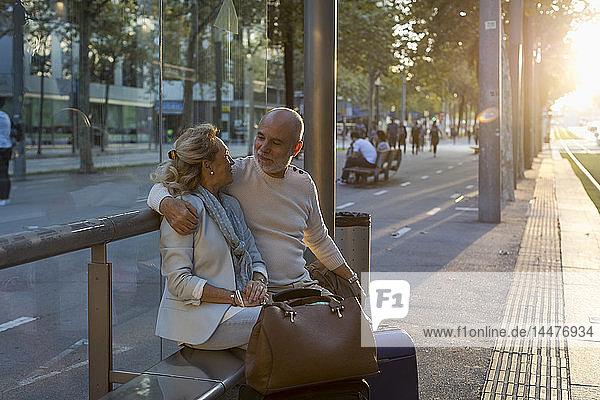 Spanien  Barcelona  älteres Ehepaar mit Gepäck sitzt bei Sonnenuntergang an der Straßenbahnhaltestelle in der Stadt