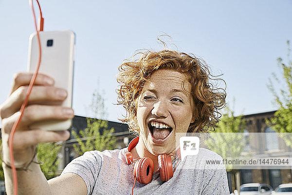 Verspielte junge Frau mit Kopfhörern  die ein Selfie in städtischer Umgebung macht