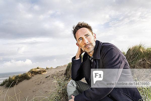In den Dünen sitzender Mann
