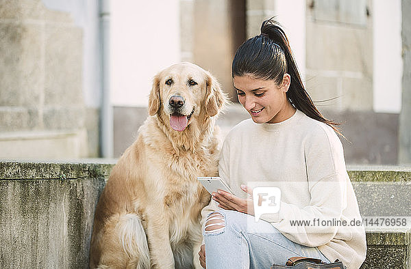 Young woman with her Golden retriever dog on stairs outdoors using cell phone