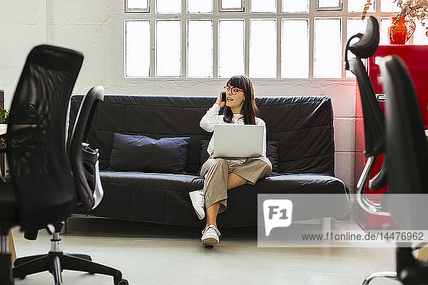 Junge Frau sitzt im Büro auf einer Couch und benutzt Handy und Laptop