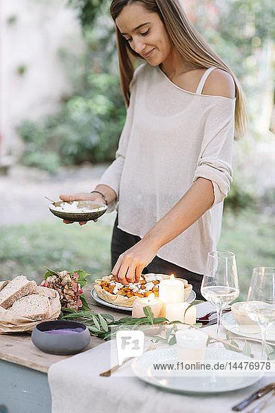 Frau bereitet ein romantisches Essen bei Kerzenlicht im Freien zu