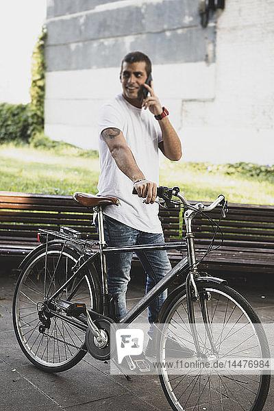 Junger Mann mit Fahrrad und Handy unterwegs