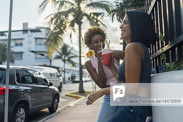 USA  Florida  Miami Beach  zwei glückliche Freundinnen bei einem Erfrischungsgetränk in der Stadt