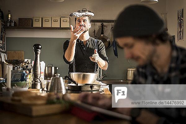Ein Mann bereitet Brotteig zu  während der andere sein digitales Tablett benutzt
