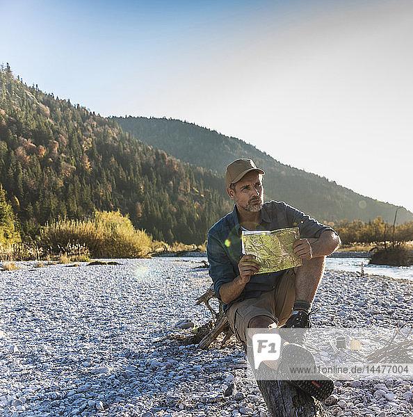 Erwachsener Mann mit Karte am Flussufer