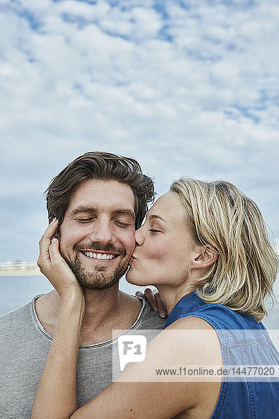 Glückliches junges Paar küsst sich am Strand