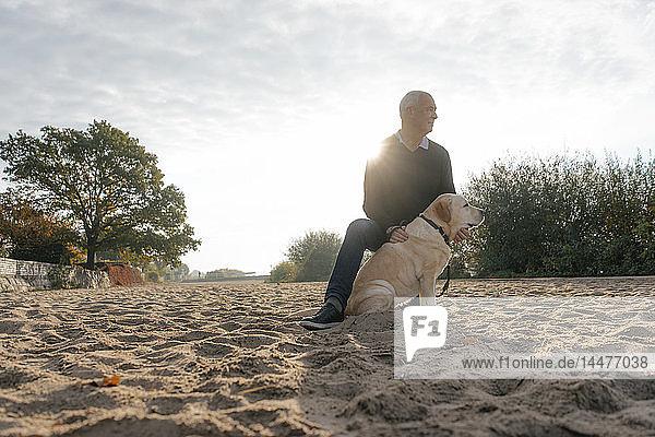 Deutschland,  Hamburg,  älterer Mann mit Hund am Elbstrand