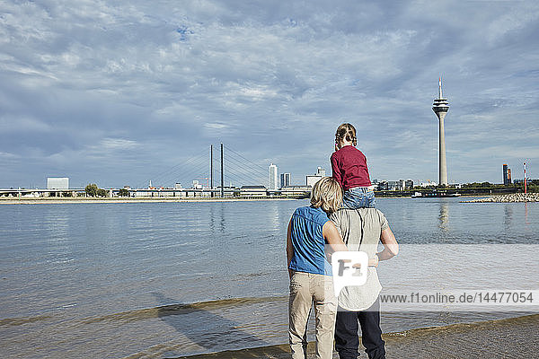 Germany  Duesseldorf  family with daughter standing at Rhine riverbank