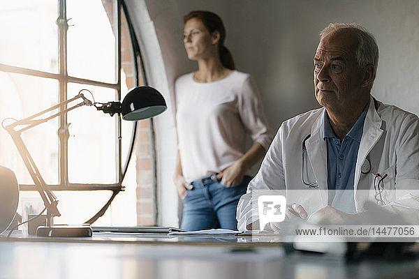 Seriöser Oberarzt am Schreibtisch sitzend in medizinischer Praxis mit Frau im Hintergrund